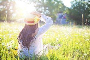 女性・草原・座る・帽子