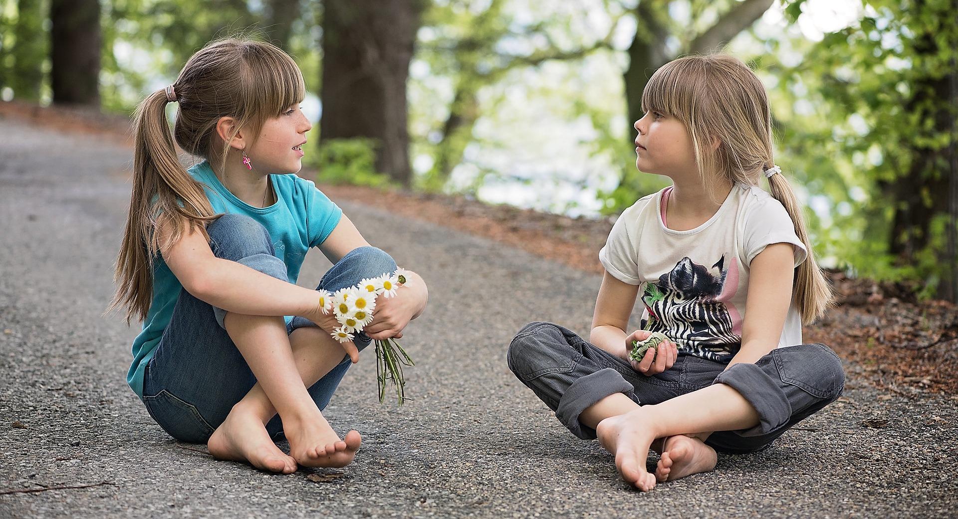 女の子が二人座って会話している画像